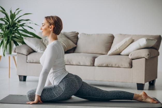 Jeune femme pratiquant le yoga à la maison sur le tapis