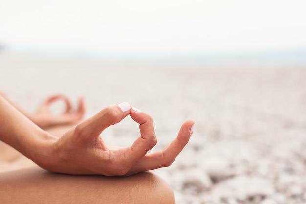 Jeune femme pratiquant le yoga sur la plage gros plan des mains gyan mudra et position du lotus