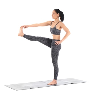 Jeune femme pratiquant le yoga sur une surface blanche