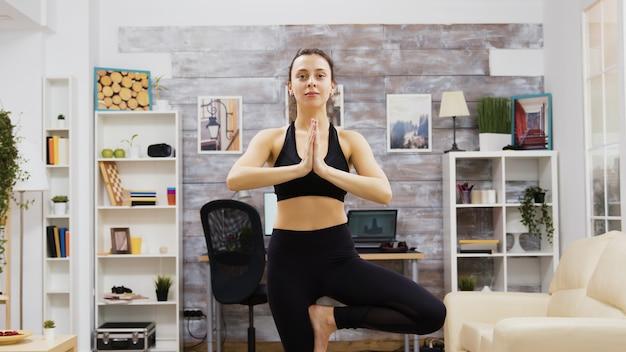 Une jeune femme pratique le bien-être en faisant du yoga dans le salon.