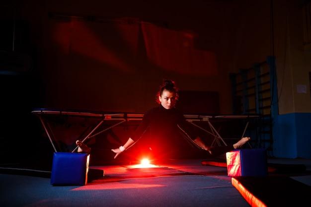 La jeune femme pratique la séance de ficelle. fille sportive faisant de la gymnastique dans la salle de gym. mode de vie actif
