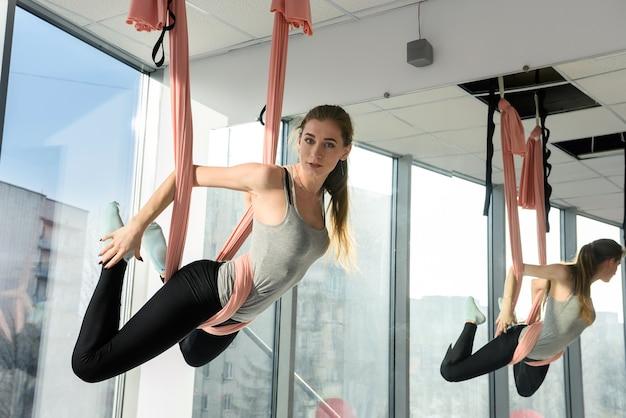 Jeune femme pratique le yoga aérien en studio