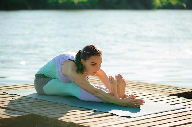 Jeune femme pratique le yoga au bord du lac.