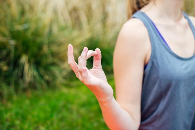 Jeune femme pratique le yoga et médite en position du lotus dans le parc