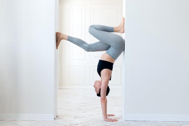 Une jeune femme pratique le yoga et se tient debout sur ses bras dans l'arche d'une pièce lumineuse. jeune femme yogi séduisante pratiquant le concept d'yoga.