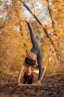 Jeune femme à pratiquer des exercices d'yoga au parc automne avec les feuilles jaunes. mode de vie sportif et récréatif