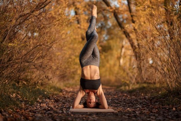 Jeune femme à pratiquer des exercices d'yoga au parc automne avec les feuilles jaunes.