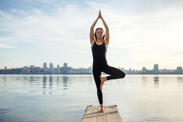 Jeune femme, pratiquer, yoga, exercice, jetée bois, calme, ville, sport, récréation, ville, précipiter