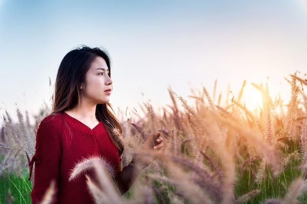 Jeune femme et pré au coucher du soleil.