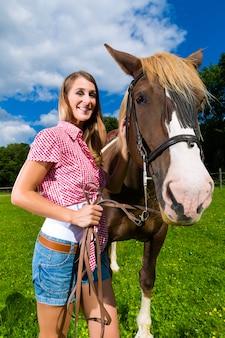 Jeune femme sur le pré avec cheval