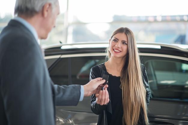 Jeune femme prenant les clés de sa voiture dans une salle d'exposition