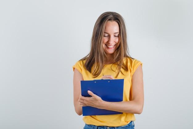 Jeune femme prenant des notes sur le presse-papiers en t-shirt, short et à occupé