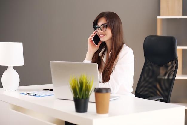 Jeune femme prenant des notes tout en parlant au téléphone portable.