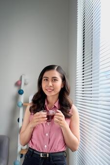 Jeune femme prenant une pause thé debout près de la fenêtre du bureau.