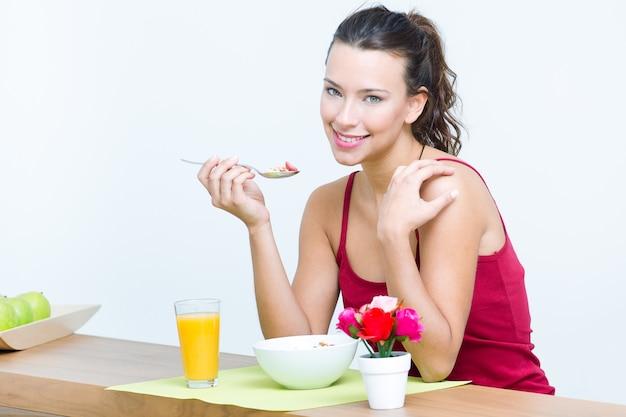 Jeune femme prenant le petit-déjeuner à la maison
