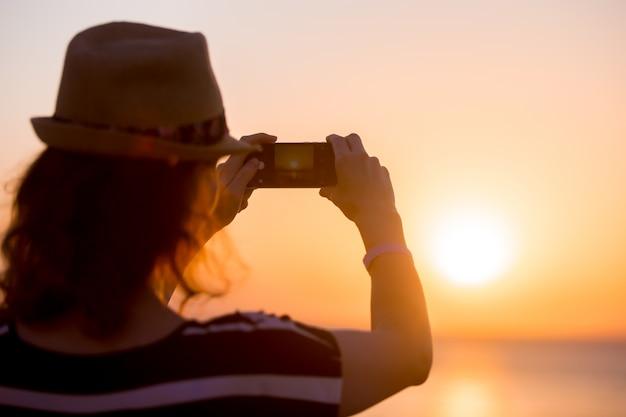 Jeune femme prenant photo du coucher de soleil sur la mer