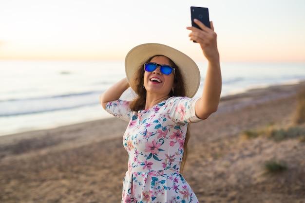 Jeune femme prenant une photo de la mer et du coucher du soleil avec un téléphone portable ou un appareil photo numérique pour smartphone pour poster à