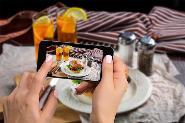 Une jeune femme prenant une photo de nourriture sur un smartphone, photographiant un repas avec un appareil photo mobile. conçu pour les réseaux sociaux. téléphone portable vue de dessus
