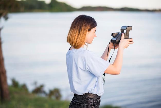 Jeune femme prenant des photos du lac