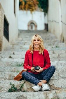 Jeune femme prenant des photos avec un vieil appareil photo dans une belle ville.