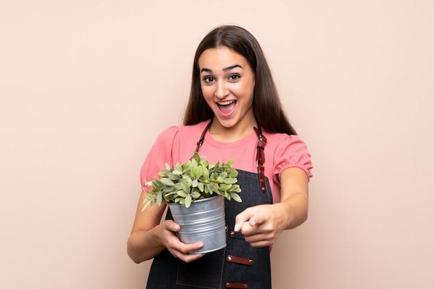 Jeune femme prenant un pot de fleurs et pointant vers l'avant