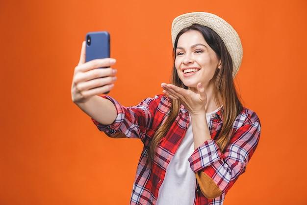 Jeune femme prenant selfie sur la caméra de son téléphone, portant une tenue d'été décontractée et un chapeau