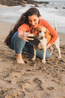Jeune femme prenant selfie avec chien
