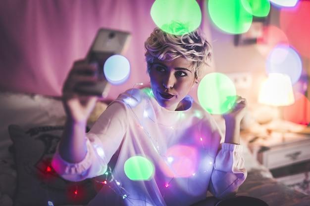 Jeune femme prenant un selfie dans sa chambre avec des lumières de noël