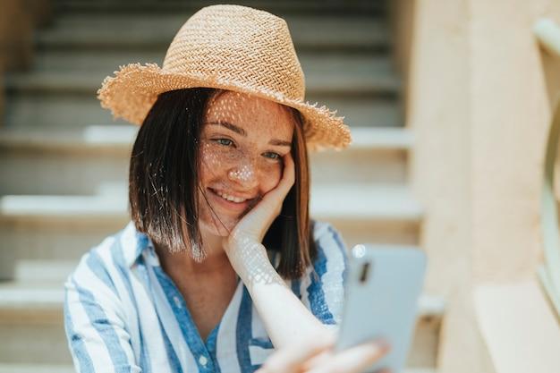 Jeune femme prenant un selfie à l'extérieur