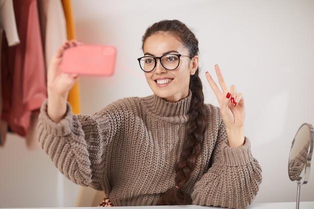 Jeune femme prenant selfie à la maison