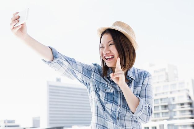 Jeune femme prenant un selfie sur smartphone