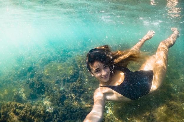 Jeune femme prenant selfie sous l'eau