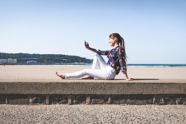 Jeune femme prenant un selfie avec un téléphone portable au bord de la plage