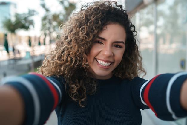 Jeune femme prenant des selfies debout à l'extérieur dans la rue. notion urbaine.