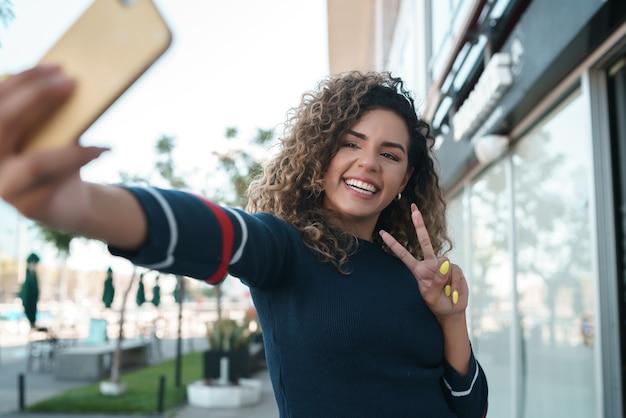 Jeune femme prenant des selfies avec son téléphone mophile tout en se tenant à l'extérieur. notion urbaine.