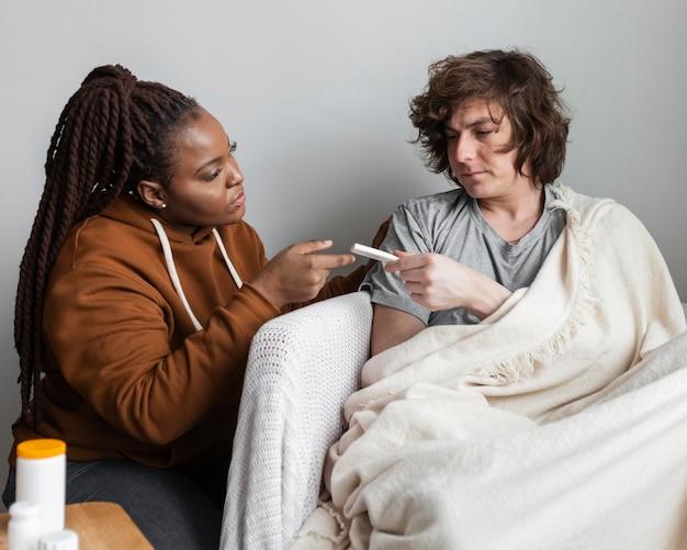Jeune femme prenant soin de son ami malade