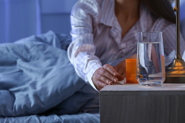 Jeune femme prenant des somnifères la nuit