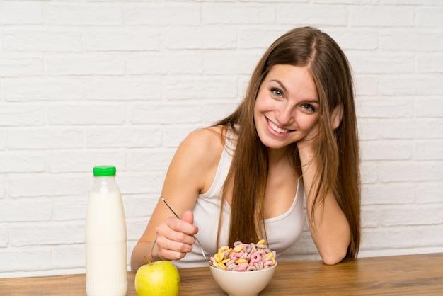 Jeune femme prenant son petit déjeuner avec bol de céréales