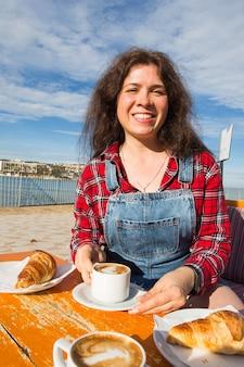 Jeune femme prenant son petit déjeuner avec croissant et café au café dans la rue en face de la mer.