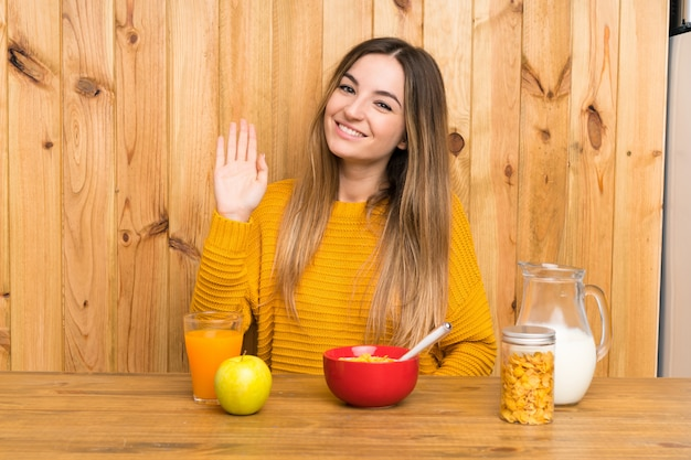 Jeune femme prenant son petit déjeuner dans une cuisine, saluant à la main avec une expression heureuse