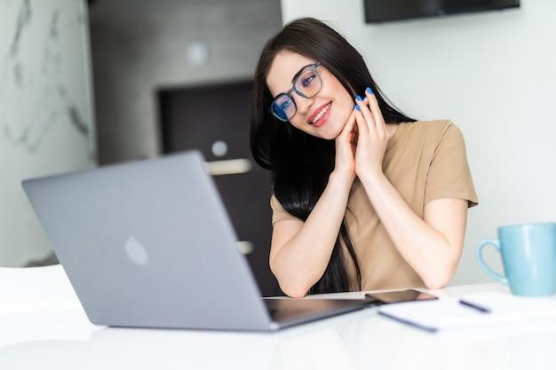 Jeune femme prenant une tasse de thé tout en utilisant son ordinateur portable dans sa cuisine