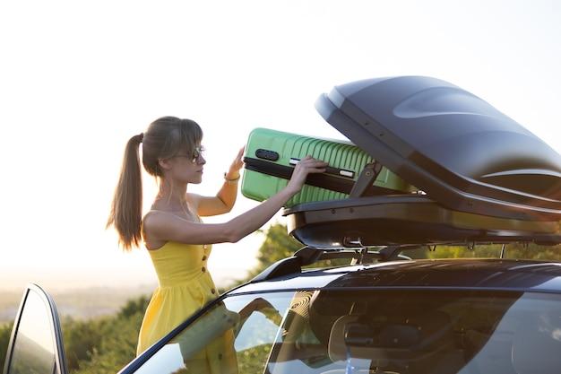Jeune femme prenant valise verte hors de la galerie de toit de voiture