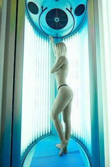 Une jeune femme prend un bain de soleil dans un solarium.