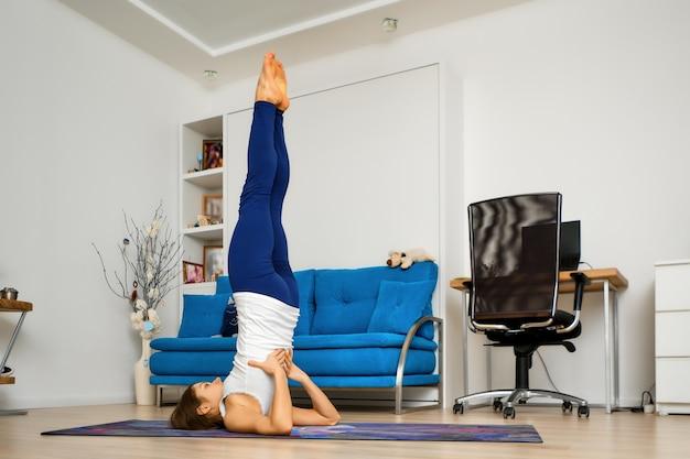 Jeune femme prend en charge la pose de yoga shoulderstand