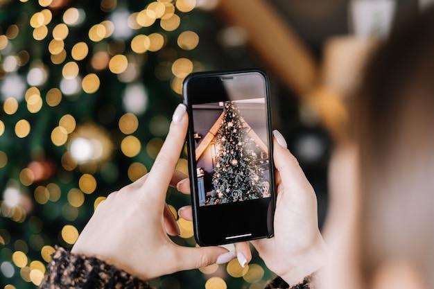 Jeune femme prend des photos de sapin de noël sur smartphone. fermer