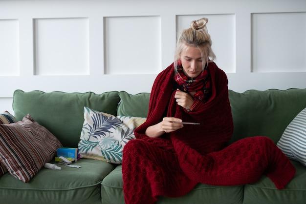 Une jeune femme prend sa température corporelle et regarde le thermomètre.