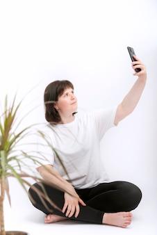 Jeune femme prend selfie sur téléphone. portrait de femme brune avec téléphone sur fond blanc. blogueur.