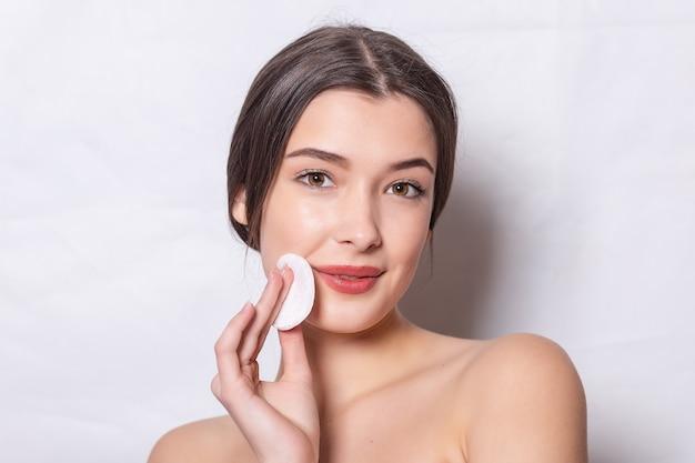 La jeune femme prend soin de la peau du visage. la fille enlève le maquillage avec une boule de coton du visage. une jeune femme nettoie la peau des cosmétiques à l'aide d'un coton-tige. concept de soins de la peau.