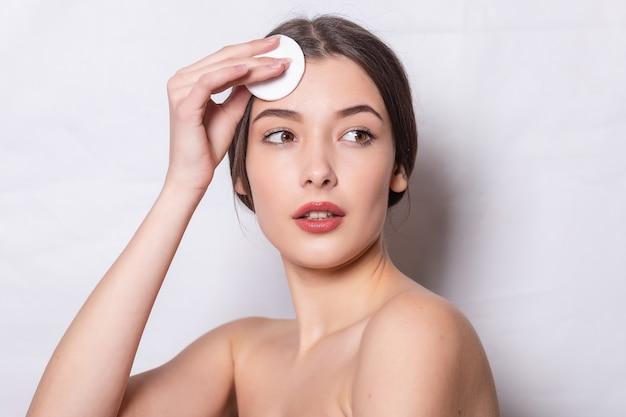 La jeune femme prend soin de la peau du visage. la jeune fille s'occupe de la relaxation de la peau du visage. belle jeune femme brune avec une peau fraîche et propre à l'aide d'un coton. concept de jeunesse et de soins de la peau.