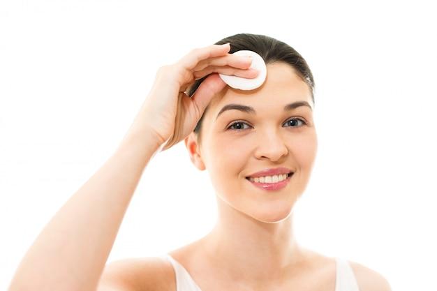 Jeune femme prend soin de la relaxation de la peau du visage, loisirs, cou, innocence, lumineux, serein, sexualité, femme à l'aide de coton